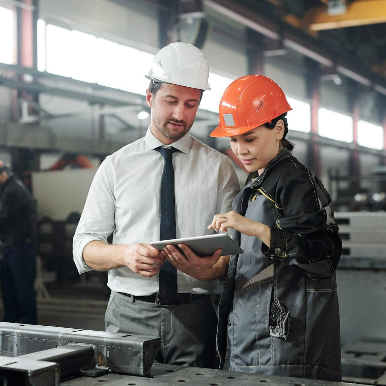 asian-metalworking-specialist-discussing-technical-sketch-with-engineer-while-they-using-engineering-app-tablet